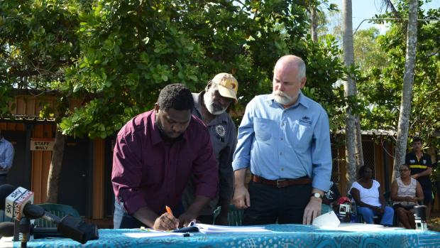 Signatories of the Tiwi Land Trust sign the Pirlangimpi Township lease as Greg Roche, Executive Director of Township Leasing looks on